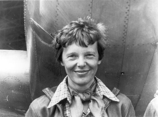 1200px-Amelia_Earhart_standing_under_nose_of_her_Lockheed_Model_10-E_Electra,_small